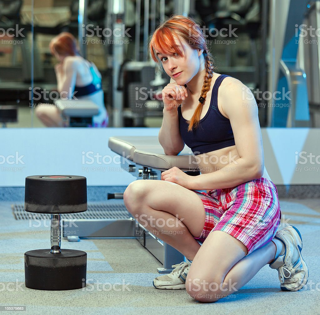 Perplexed female bodybuilder siitting before huge dumbbell royalty-free stock photo