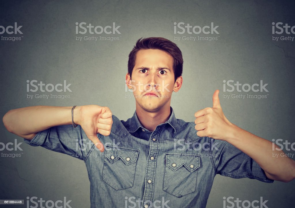 Perplexed man with thumbs down thumbs up gesture stock photo