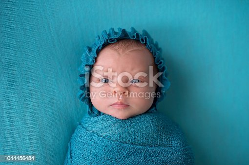 An alert, three week old, newborn baby girl wearing a turquoise blue bonnet with a perplexed expression.