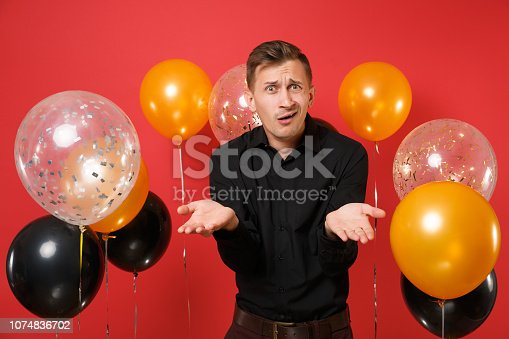 istock Perplexed young man in black classic shirt spreading hands on bright red background air balloons. St. Valentine's, International Women's Day, Happy New Year, birthday mockup holiday party concept. 1074836702