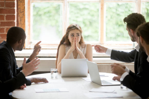 Perplexed young woman looking at coworkers pointing fingers at her. stock photo
