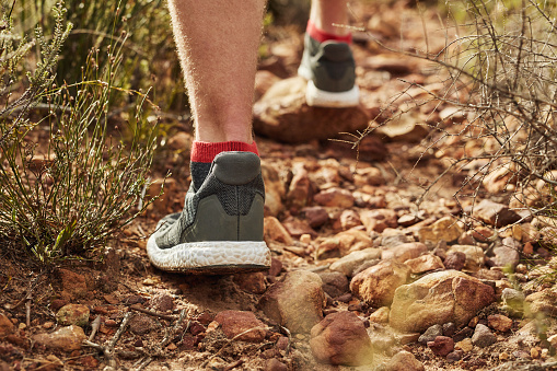 Cropped shot of an unrecognisable man walking along on a rocky hiking trail