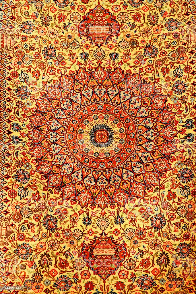 Persian carpet with reds yellows and oranges stock photo
