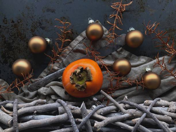 Persimmon amidst Christmas decorations stock photo