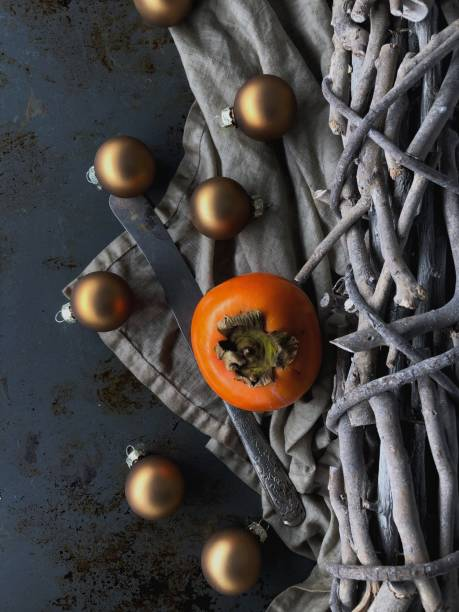 Persimmon and knife amidst Christmas decorations stock photo