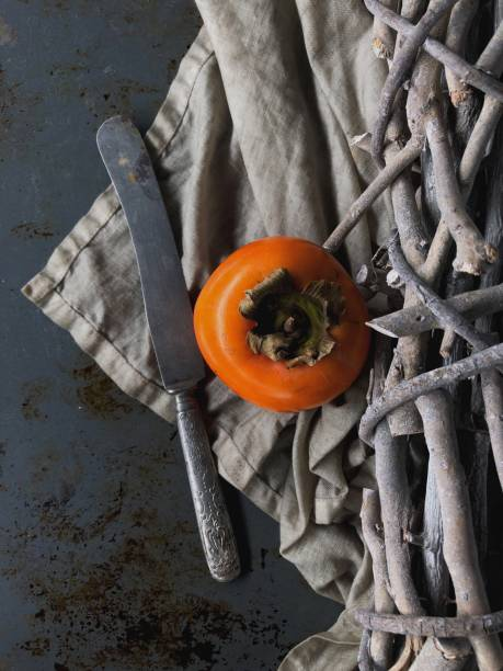 Persimmon and knife on dark table stock photo
