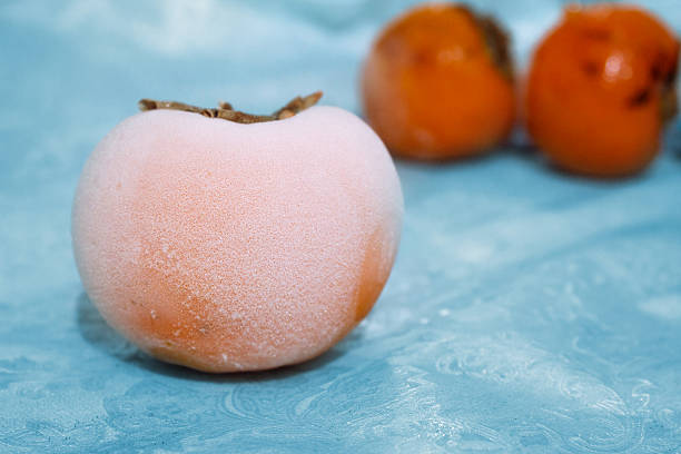Persimmon covered with frost. stock photo