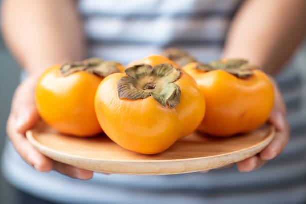 kaki früchte von hand halten - sharonfrucht stock-fotos und bilder