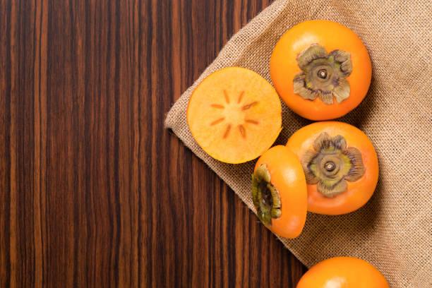 kaki früchte auf rustikalen sack und holztisch - sharonfrucht stock-fotos und bilder
