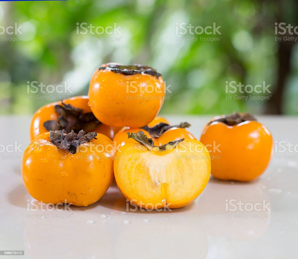 Persimmons on tile table in the garden royalty-free stock photo