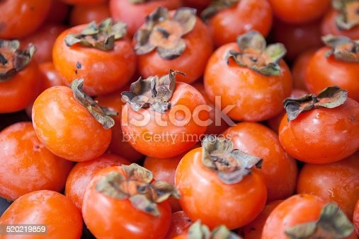 A basket full of orange persimmons.