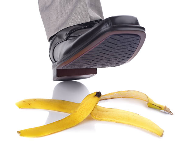 A person about to slip on a banana peel Businessman foot about to slip and fall on a banana skin banana peel stock pictures, royalty-free photos & images
