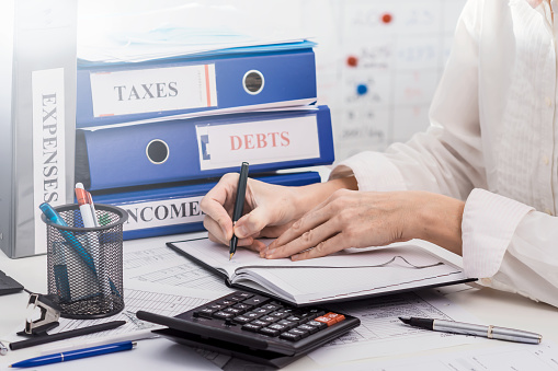 Person accounting incomes and expenses of a company, calculating taxes, concept of work in accountant department, closeup view