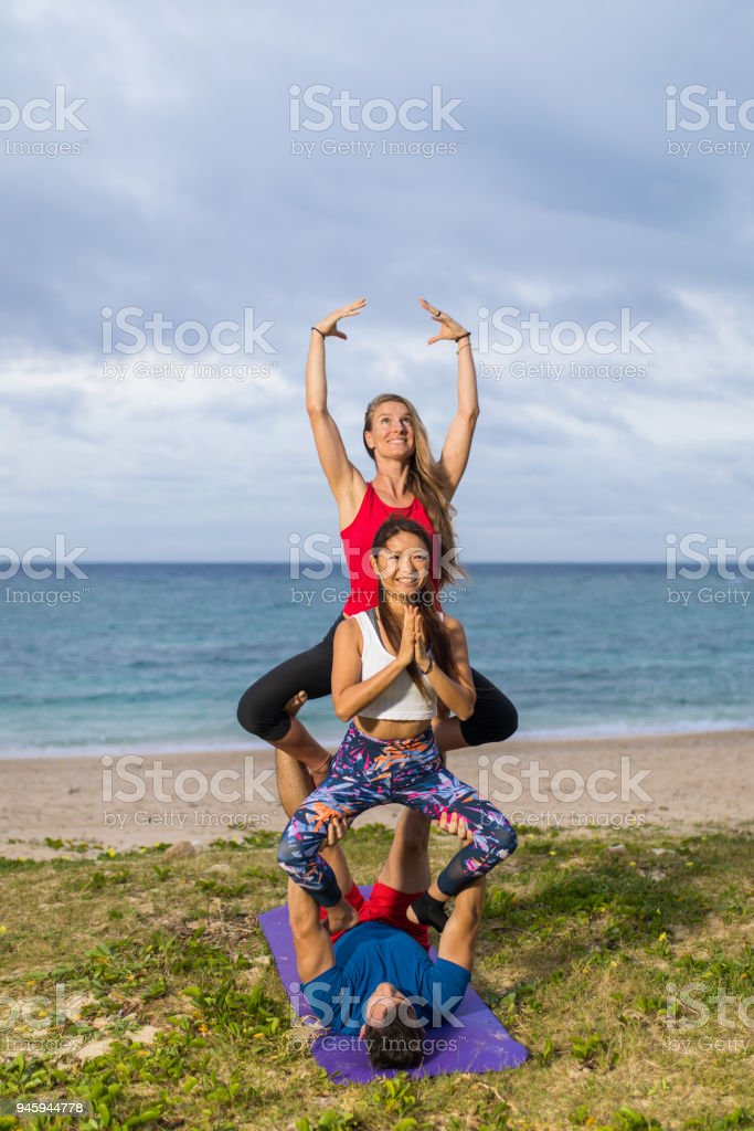 3 Person Acrobatic Yoga Pose By The Sea Royalty Free Stock Photo