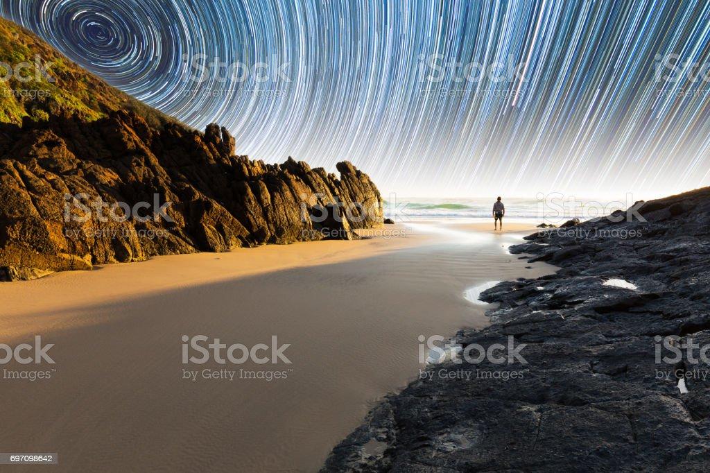 Person and coastal star trail stock photo