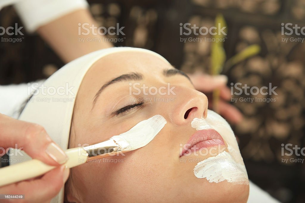Person applying a facial mask on a woman stock photo