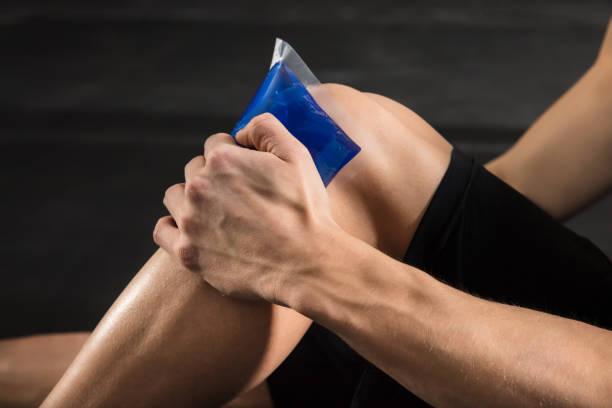 person applying ice bag on knee - crioterapia foto e immagini stock