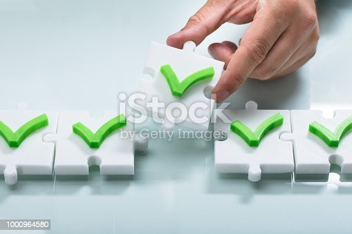 Close-up of a person's hand arranging green check mark sign in a row