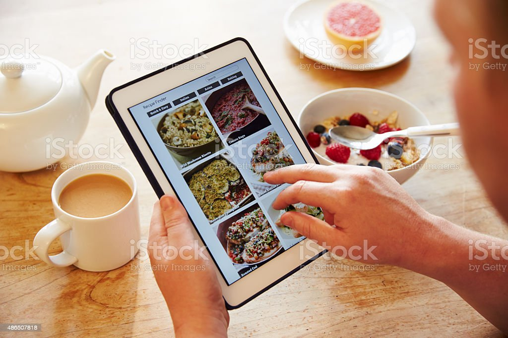 Person At Breakfast Looking At Recipe App On Digital Tablet stock photo