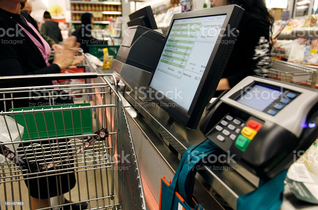 A person at the cash register of a supermarket stock photo