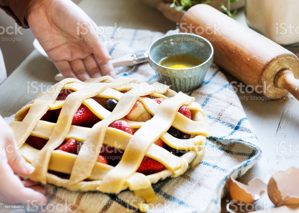 A person baking fruit pie food photography recipe idea stock photo