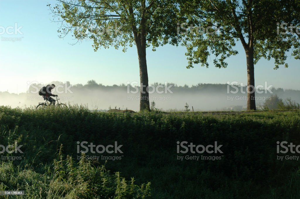 Person Biking on Dutch Levee During Spring royalty-free stock photo