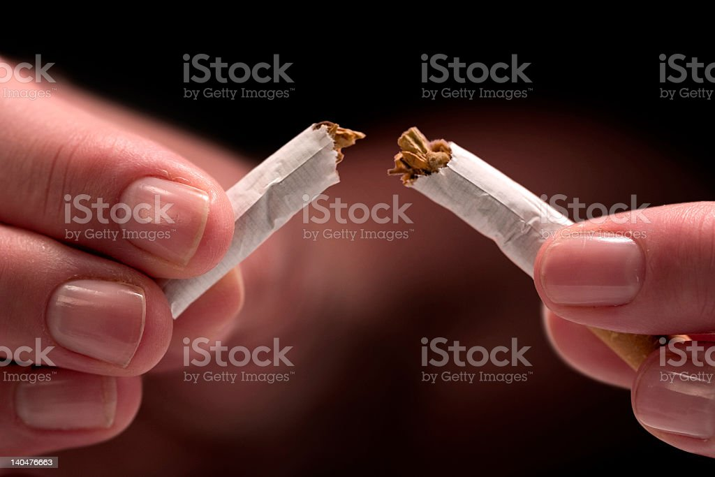 Person breaking a cigarette in two depicting addiction break royalty-free stock photo