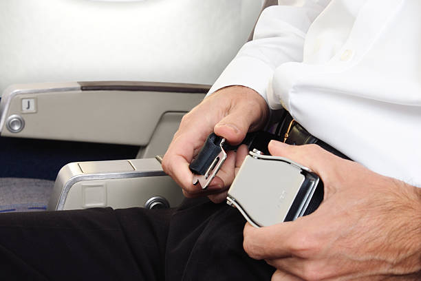 Person buckling an airplane seatbelt stock photo