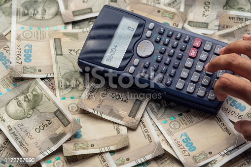 Business man pressing calculator, calculating the conversion rate of indian rupee money as a return of financial investment or monthly bills & expenses with copy space.