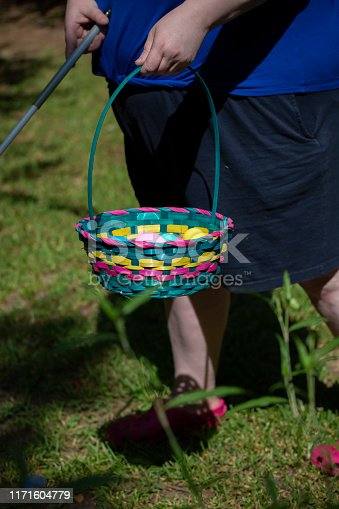 Blind woman carrying a cane and a colorful Easter basket filled with yellow, blue, green, purple, and pink eggs
