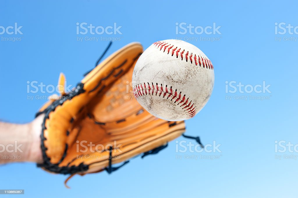 Person catching baseball with blue sky background stock photo