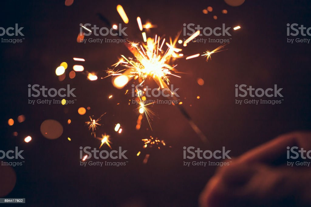 Person celebrating at night by holding sparkler - New Year Christmas Celebration stock photo