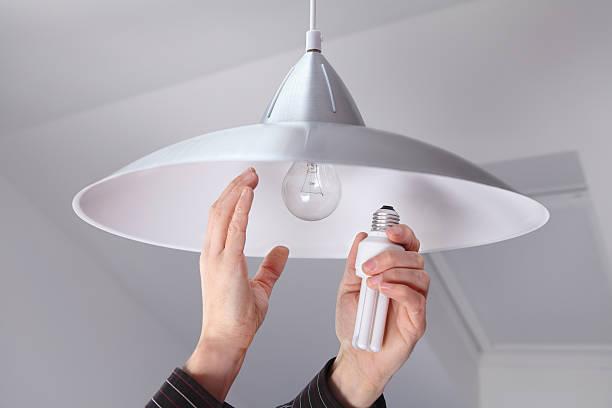 person ändern, glühbirnen, um energie zu sparen - glühbirne auswechseln stock-fotos und bilder