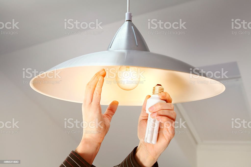 Person changing bulbs to save energy stock photo