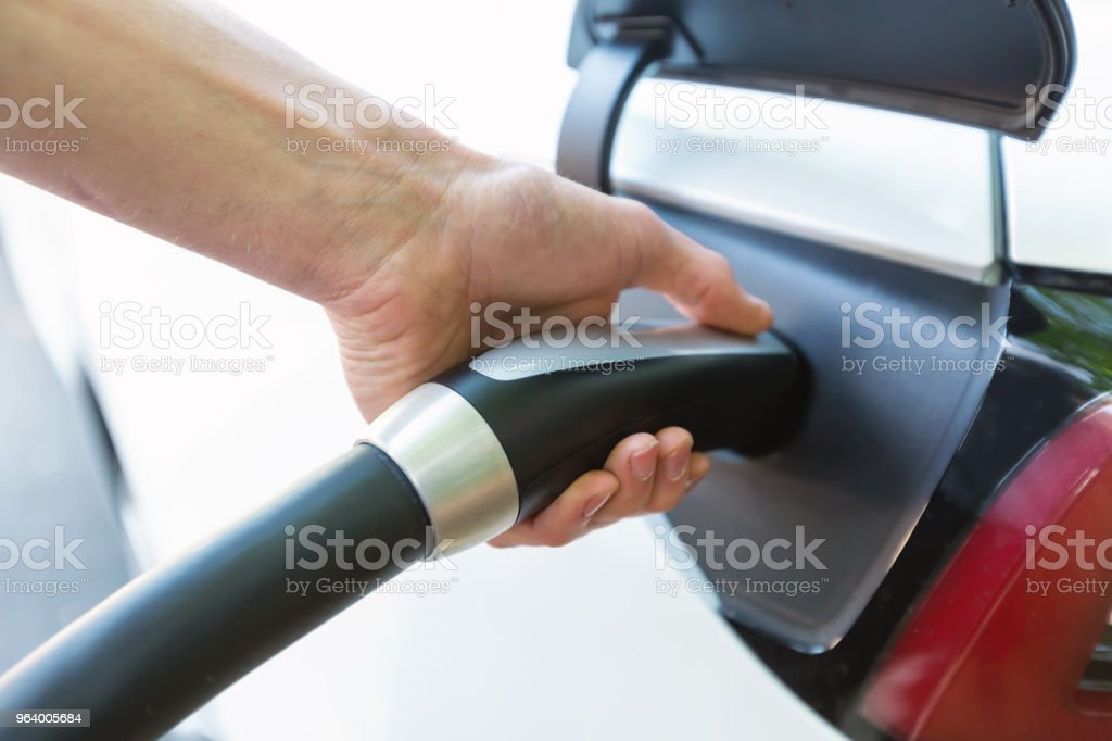 Person charging an electric vehicle - Royalty-free Adult Stock Photo