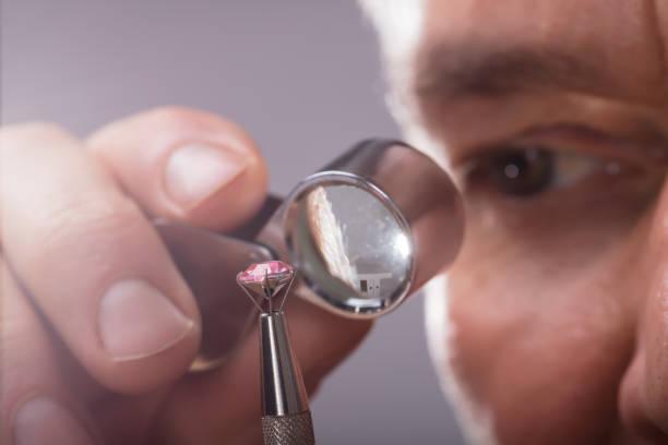 Person Checking Diamond Through Magnifying Loupe Close-up Of A Person's Hand Checking Diamond Through Magnifying Loupe jeweller stock pictures, royalty-free photos & images