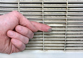 Person checks the contamination of the ventilation grille