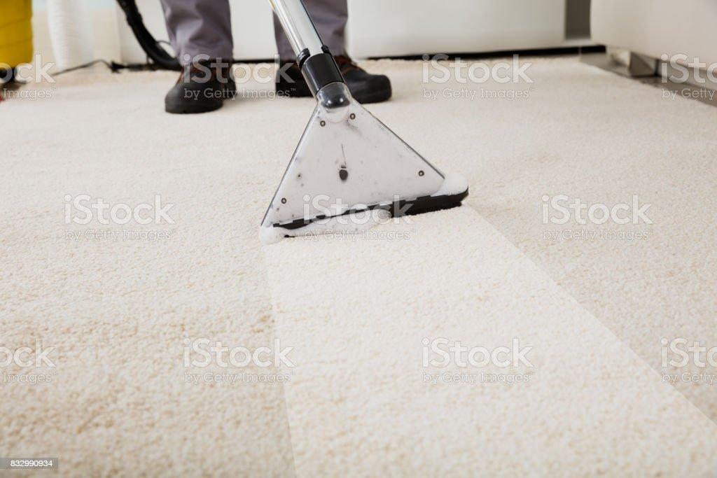 Persona limpieza de alfombra con la aspiradora - foto de stock