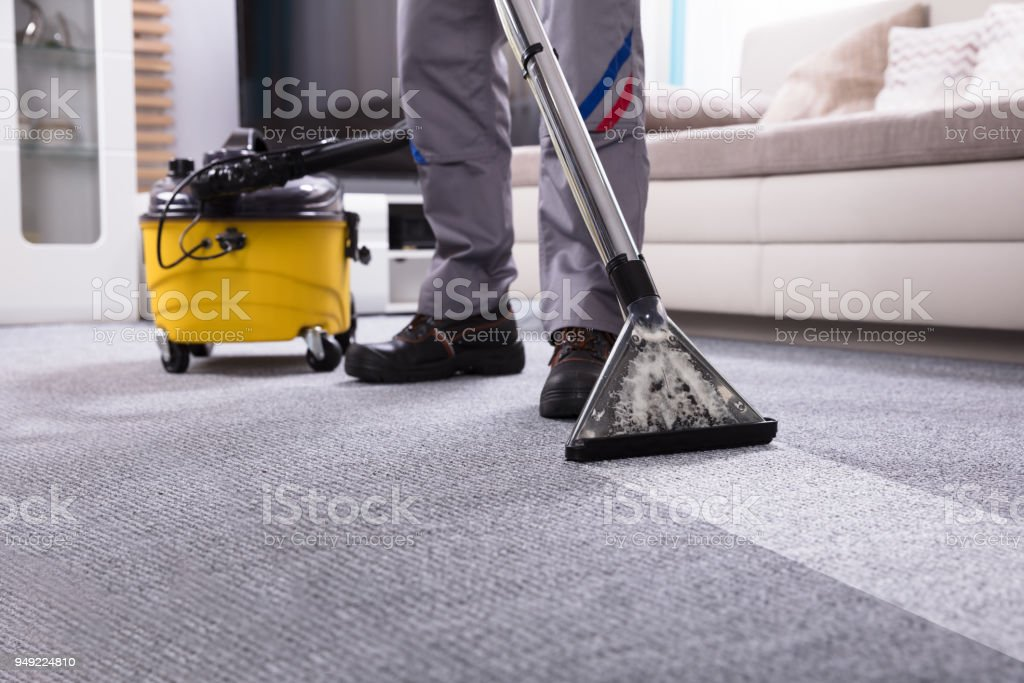 Person Cleaning Carpet With Vacuum Cleaner royalty-free stock photo