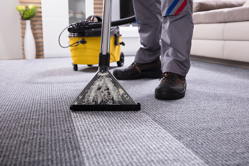 Person Cleaning Carpet With Vacuum Cleaner Stock Photo