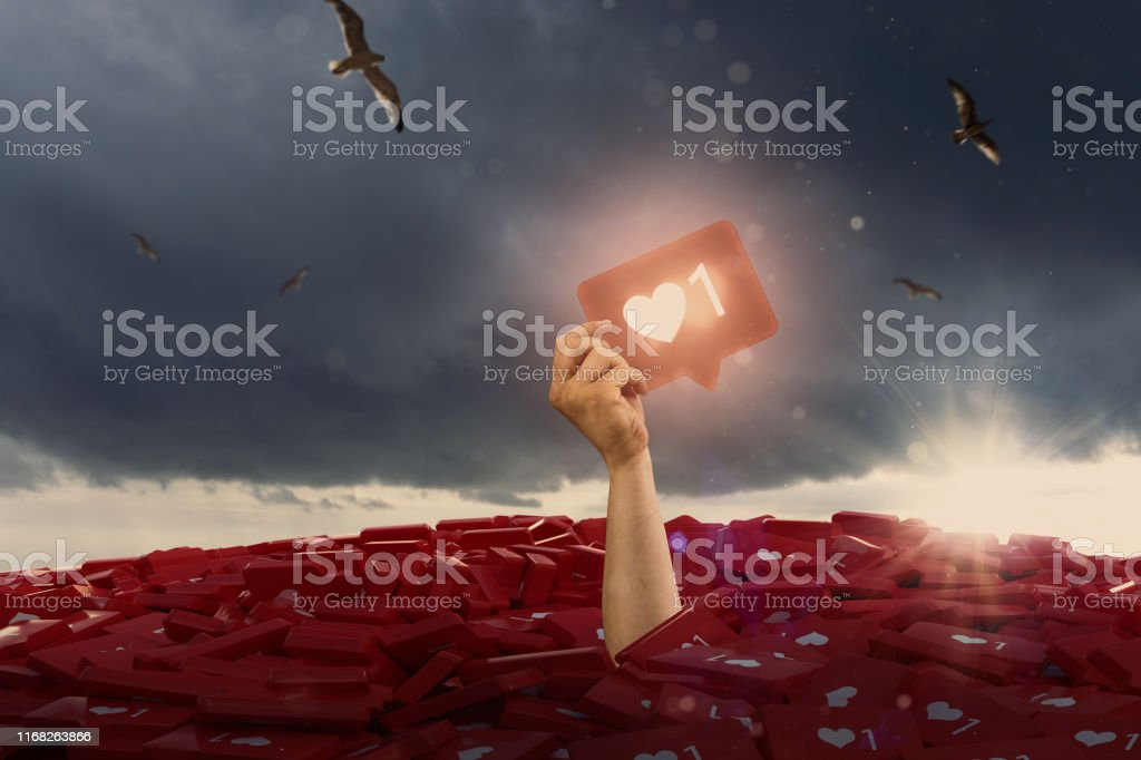 person holding glowing social media like button into the sky