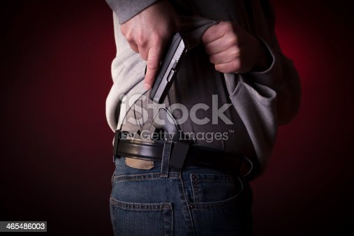 A man drawing a conceal carry pistol from an inside the waistband holster IWB.