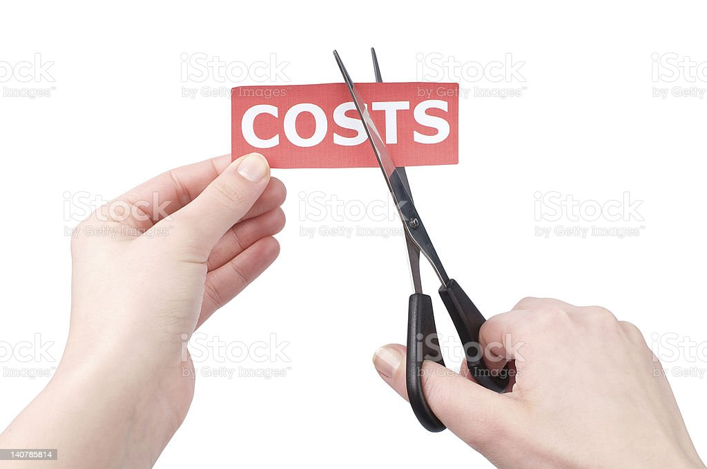 A person cutting the costs word with scissors stock photo