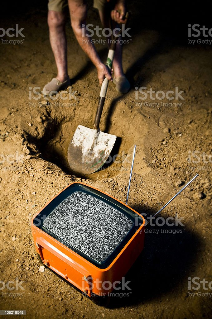 Person Digging Hole Beside Old Television stock photo