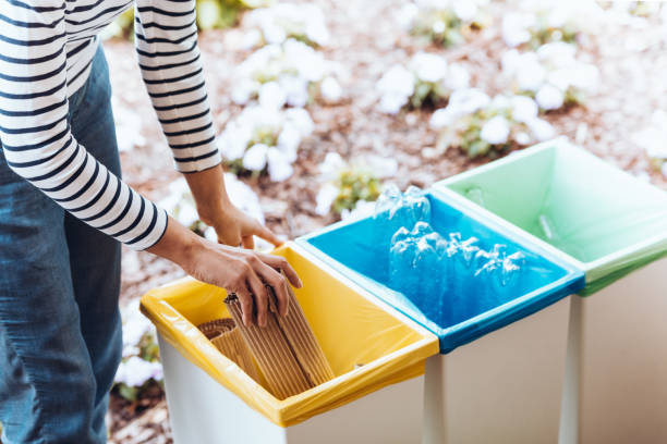 person disposing paper to bin - recycling bin stock photos and pictures