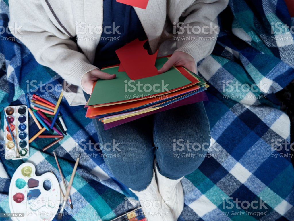 Person wearing warm domestic clothing is sitting on the checkered...