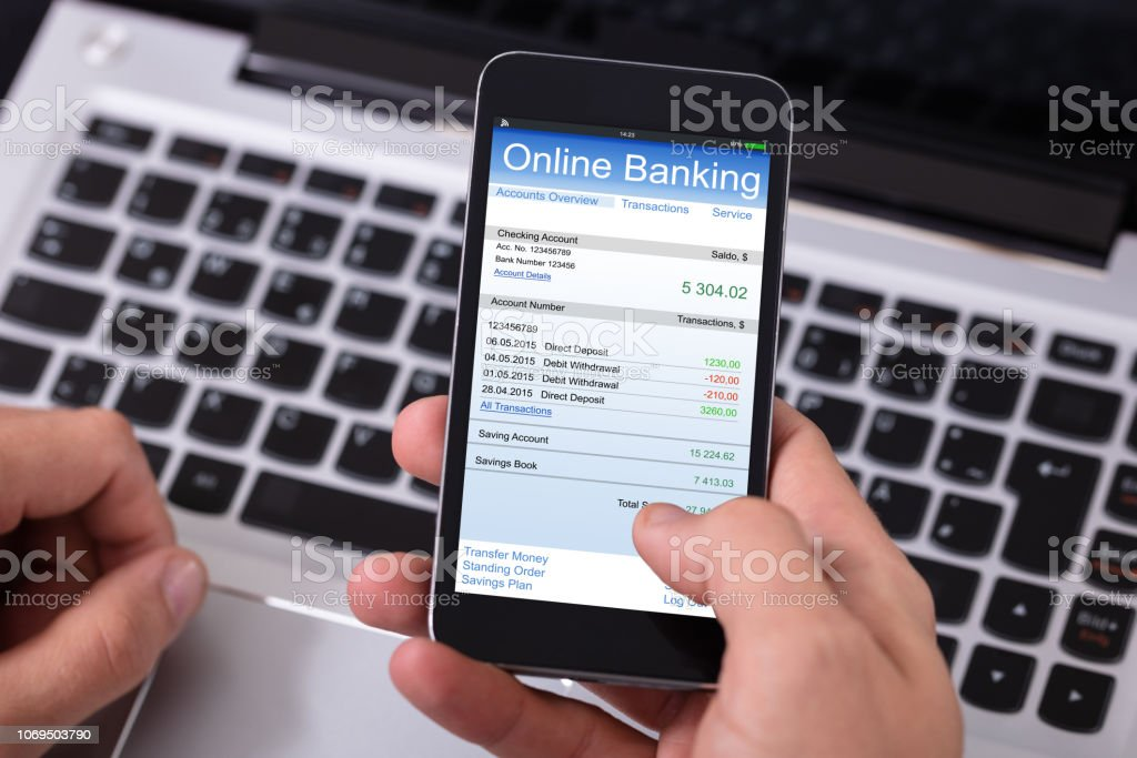 Close-up Of A Person Doing Online Banking On Mobile Phone Over Laptop