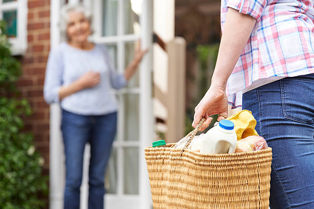 Persona haciendo compras por edad avanzada vecino - foto de stock