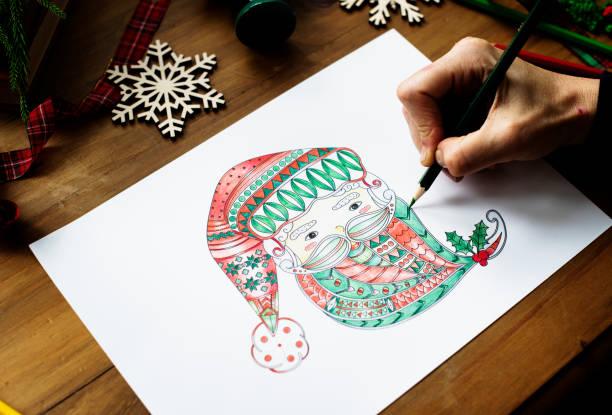 eine person, die zeichnung eines bunten weihnachtsmannes ' gesicht - ausmalbilder weihnachtsmann stock-fotos und bilder