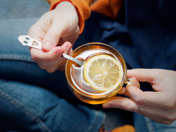 Person drinking tea with lemon stock photo